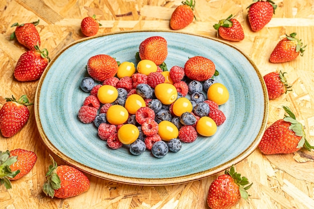 Top view of the fresh berries on a round white dish