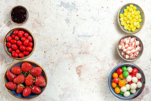 上面図白いテーブルキャンディフルーツベリーにキャンディーと新鮮なベリー