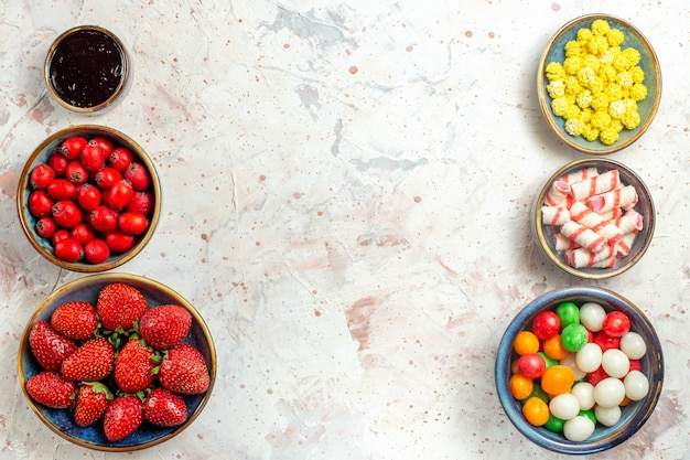 Vista dall'alto bacche fresche con caramelle sul tavolo bianco caramelle frutti di bosco