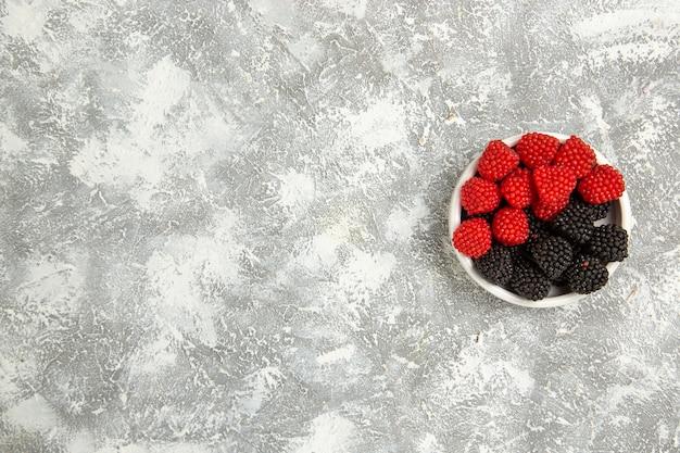 上面図新鮮なベリーは白い表面のプレートの内側に甘いキャンディーを構成しますベリーキャンディーシュガースイートケーキパイクッキー