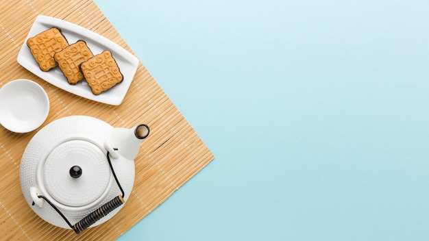 Вид сверху свежие печенья и чайник с копией пространства