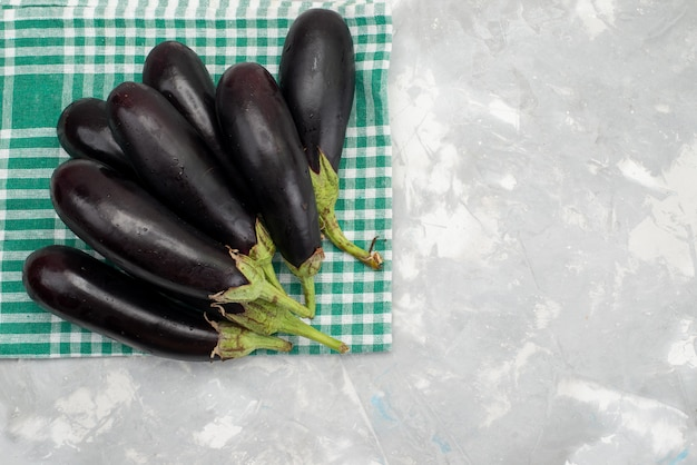 Top view fresh black eggplants ripe fresh on the bright desk vegetable food meal dish raw