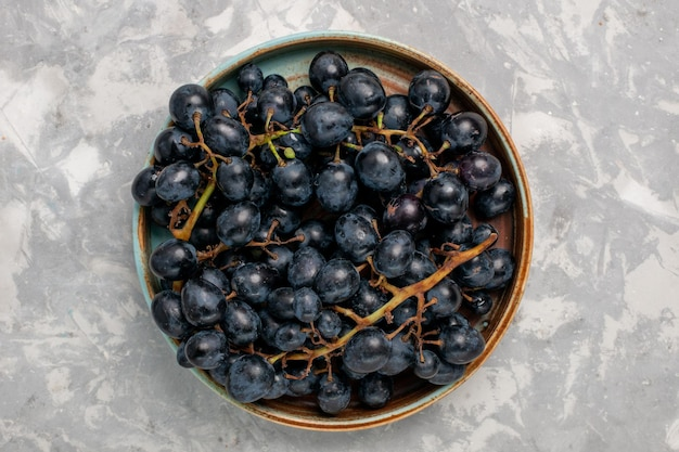 밝은 흰색 책상 위에 있는 신선한 검은 포도 즙이 많은 부드러운 달콤한 과일
