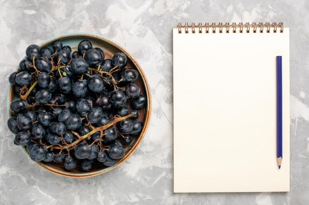 밝은 흰색 책상에 메모장이 있는 신선한 검은 포도 즙이 많은 부드러운 달콤한 과일