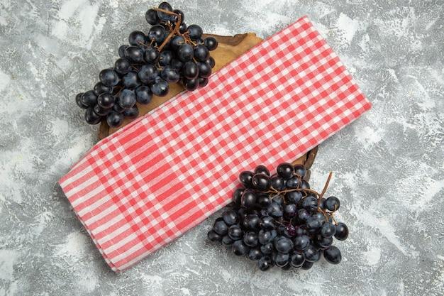Vista dall'alto uva nera fresca su sfondo bianco frutta fresca matura fresca