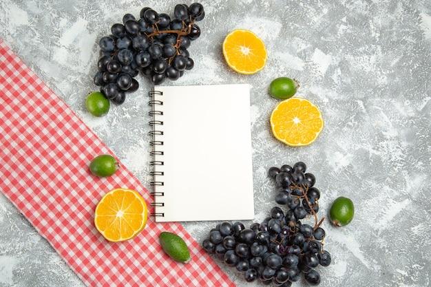 Вид сверху свежий черный виноград с блокнотом фейхоа и апельсинами на белой поверхности.