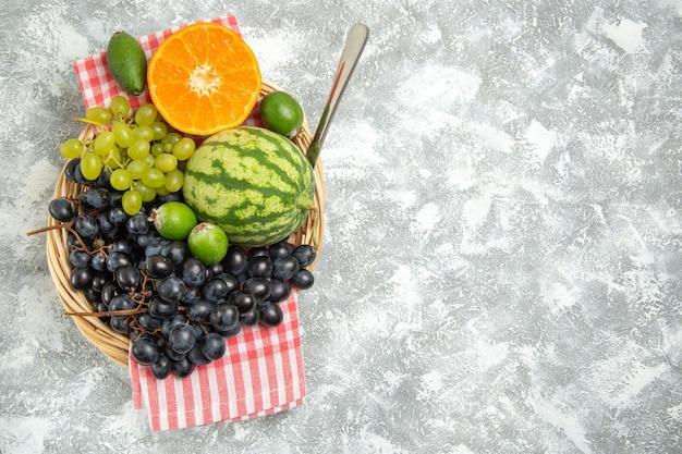 Вид сверху свежий черный виноград с апельсином и фейхоа на белой поверхности спелые спелые свежие фрукты