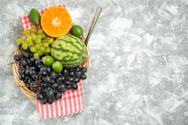 Vista dall'alto uva nera fresca con arancia e feijoa su superficie bianca frutta fresca matura dolce