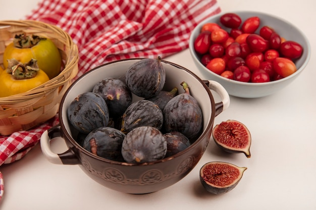 Top view of fresh black mission figs on a bowl with cornelian cherries on a bowl on a white wall