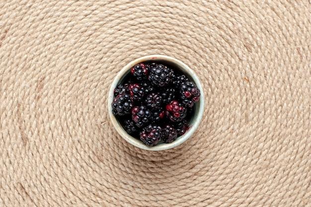 ピンクの机の上の白い小さな鍋の中の新鮮なブラックベリーの上面図。