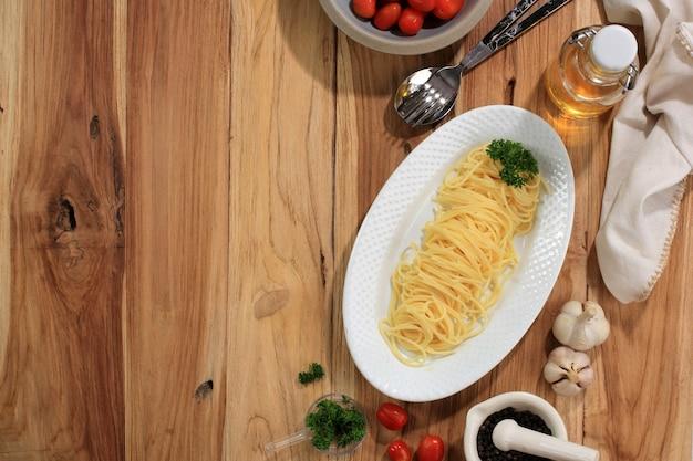 Вид сверху свежие вареные спагетти на белой тарелке, готовые к подаче с соусом. концепция здорового питания. на деревянном столе скопируйте место для текста
