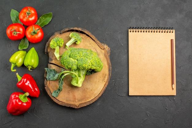 Вид сверху свежей брокколи с другими овощами на темном столе цвета спелого салата