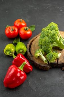 Вид сверху свежей брокколи с помидорами и болгарским перцем на темном полу цвета спелого салата