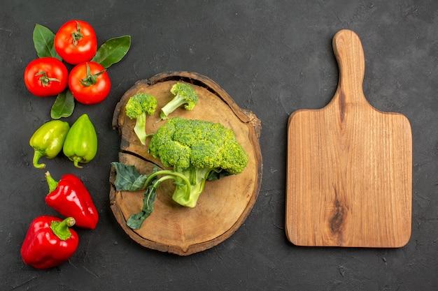 Вид сверху свежей брокколи с помидорами и болгарским перцем на темном столе салатного цвета