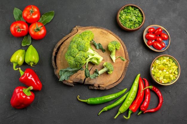 Vista dall'alto broccoli freschi con pomodori e peperoni sul colore insalata matura tavolo scuro