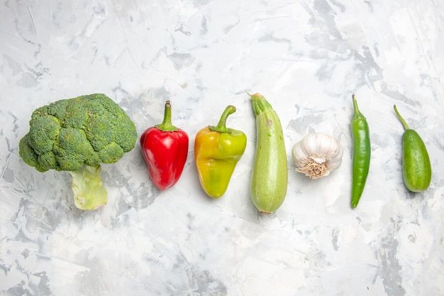 Вид сверху свежей брокколи с овощами на белом столе, салате, спелой здоровой диете