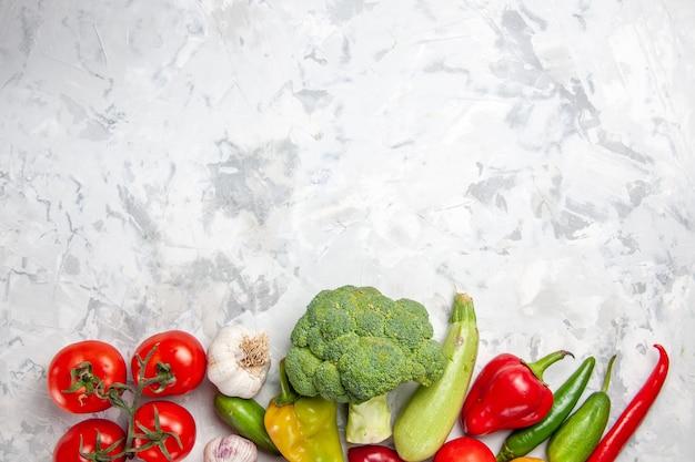 Вид сверху свежей брокколи с овощами на белом полу, диетический салат, спелое здоровье