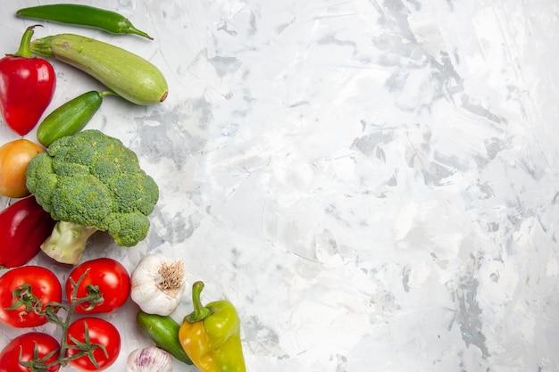 Вид сверху свежей брокколи с овощами на белом столе, диетический салат, спелое здоровье