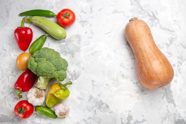 Vista dall'alto di broccoli freschi con verdure sul pavimento bianco salute dieta insalata di colore