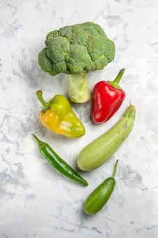 Broccoli freschi di vista superiore con le verdure sulla salute matura dell'insalata di dieta della tabella bianca