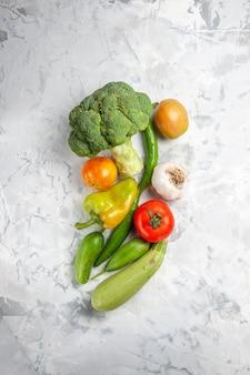 Broccoli freschi di vista superiore con le verdure sulla dieta di salute matura dell'insalata da tavola bianca
