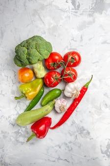 Broccoli freschi di vista superiore con le verdure sulla salute matura dell'insalata della tavola bianca