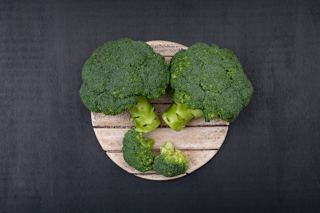 Top view fresh broccoli on wooden cutting board
