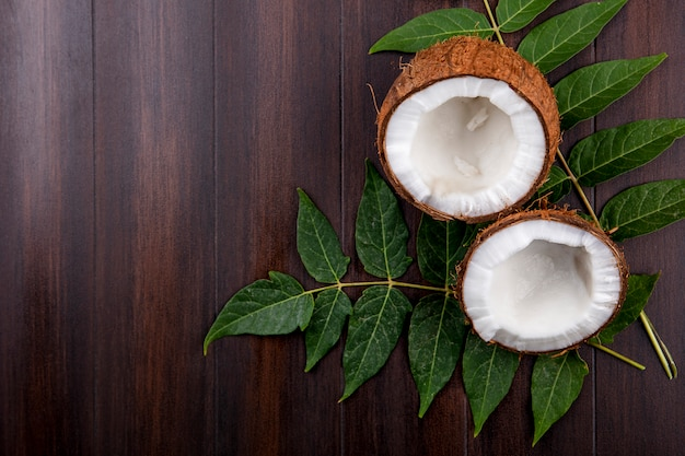 Top view of fresh and brown coconuts with leaves on wood