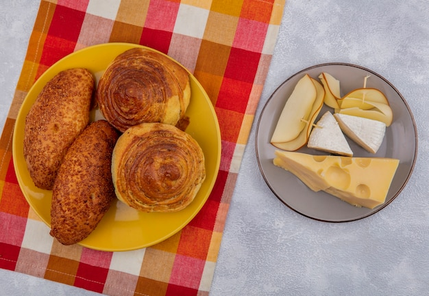 Top view of fresh buns on a yellow plate on a checked cloth with different types of cheese on a grey plate on a white background