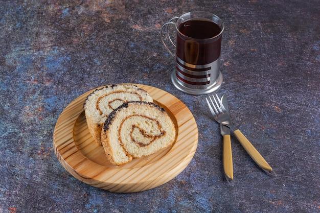 Vista dall'alto di rotoli di torta fresca con una tazza di tè su rustico