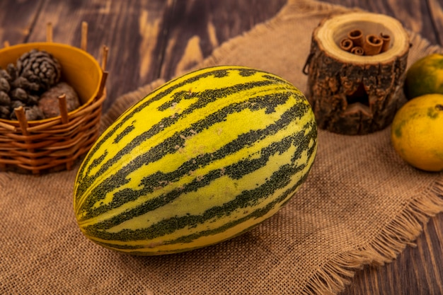 Top view of fresh cantaloupe melon on a sack cloth with cinnamon sticks with pine cones on a bucket on a wooden wall