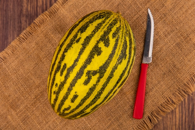 Top view of fresh cantaloupe melon on a sack cloth with knife on a wooden surface
