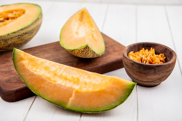 Top view of fresh cantaloupe melon slices on wood kitchen board on white wood