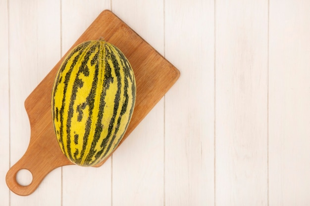 Top view of fresh cantaloupe melon on a wooden kitchen board on a white wooden surface with copy space