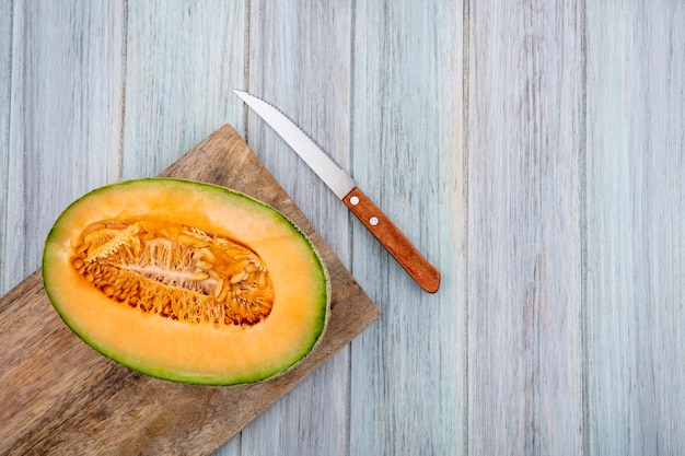 Top view fresh cantaloupe melon on wooden kitchen board with knife on grey wood with copy space
