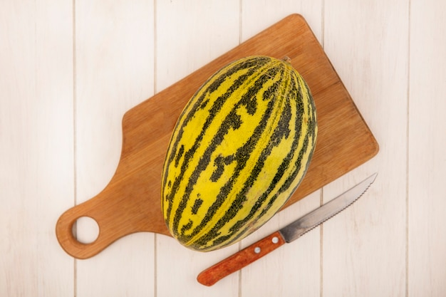 Top view of fresh cantaloupe melon on a wooden kitchen board with knife on a white wooden surface