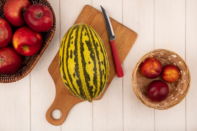 Top view of fresh cantaloupe melon on a wooden kitchen board with knife with apples on a bucket with peaches on a white wooden wall