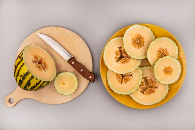 Top view of fresh cantaloupe melon on a wooden kitchen board with knife with melon slices on a yellow plate on a white wall