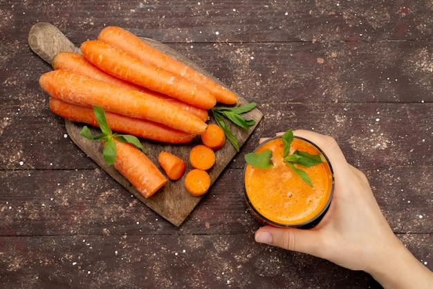 Вид сверху свежий морковный сок внутри длинного стакана с листом и вместе со свежей морковью на коричневом