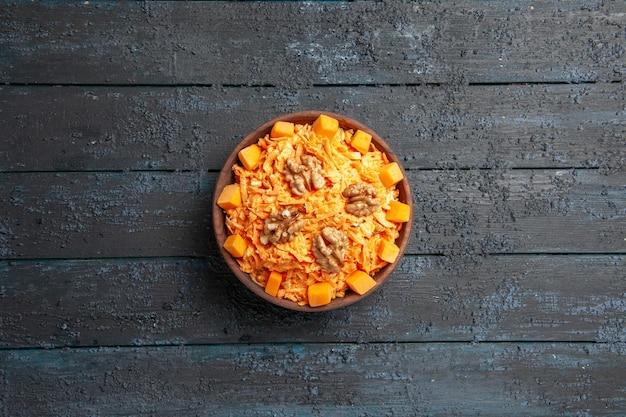 Вид сверху салат из свежей моркови тертый салат с грецкими орехами и чесноком на темном столе здоровая диета оранжевый салат спелого цвета