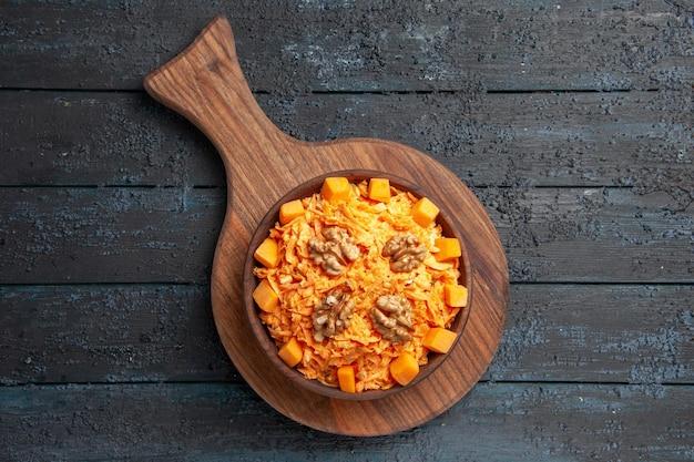 Vista dall'alto insalata di carote fresche grattugiate con noci su insalata da scrivania scura dieta per la salute delle noci di colore
