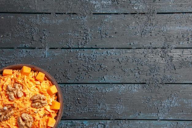 Vista dall'alto insalata di carote fresche grattugiate con noci e aglio su scrivania scura dieta salute insalata di colore maturo