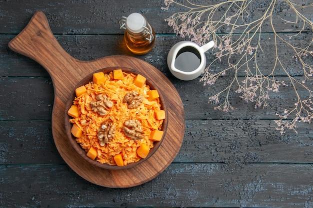 Vista dall'alto insalata di carote fresche con noci sul dado da scrivania scuro dieta salute insalata colore vegetale