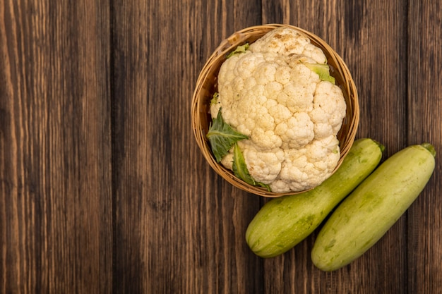 Top view of fresh cauliflower on a bucket with zucchinis isolated on a wooden background with copy space