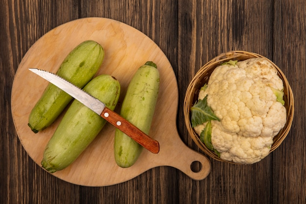 Top view of fresh cauliflower on a bucket with zucchinis isolated on a wooden kitchen board with knife on a wooden surface