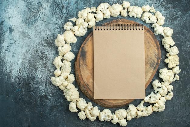 Vista dall'alto cavolfiore fresco cerchiato sul tavolo grigio chiaro foto dieta insalata di cavolo colorato