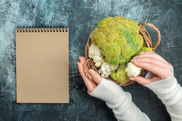 Top view fresh cauliflower inside basket on light-grey tablee