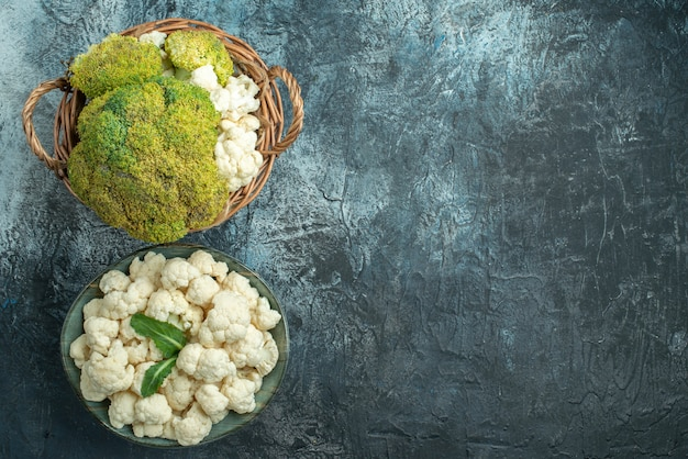 Top view fresh cauliflower inside basket and plate on light-grey table d