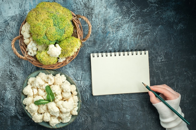 Top view fresh cauliflower inside basket and plate on a light-grey table