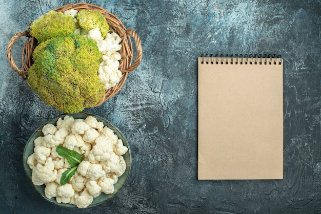 Top view fresh cauliflower inside basket and plate on light-grey table